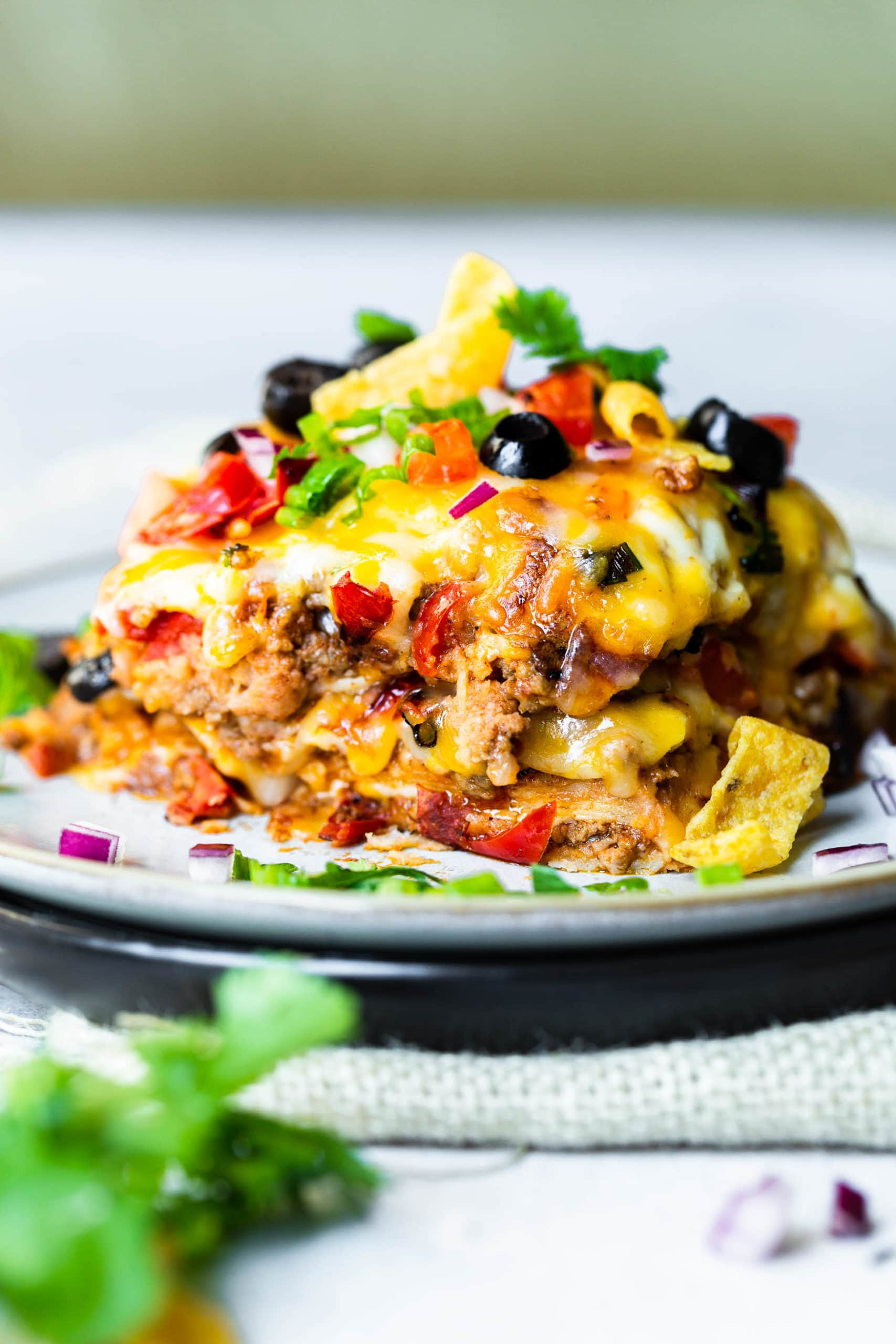 a photo of a piece of taco casserole on a saucer piled high with layers of cheesy ground beef, melted cheese on top, black beans, diced tomatoes and fresh cilantro.
