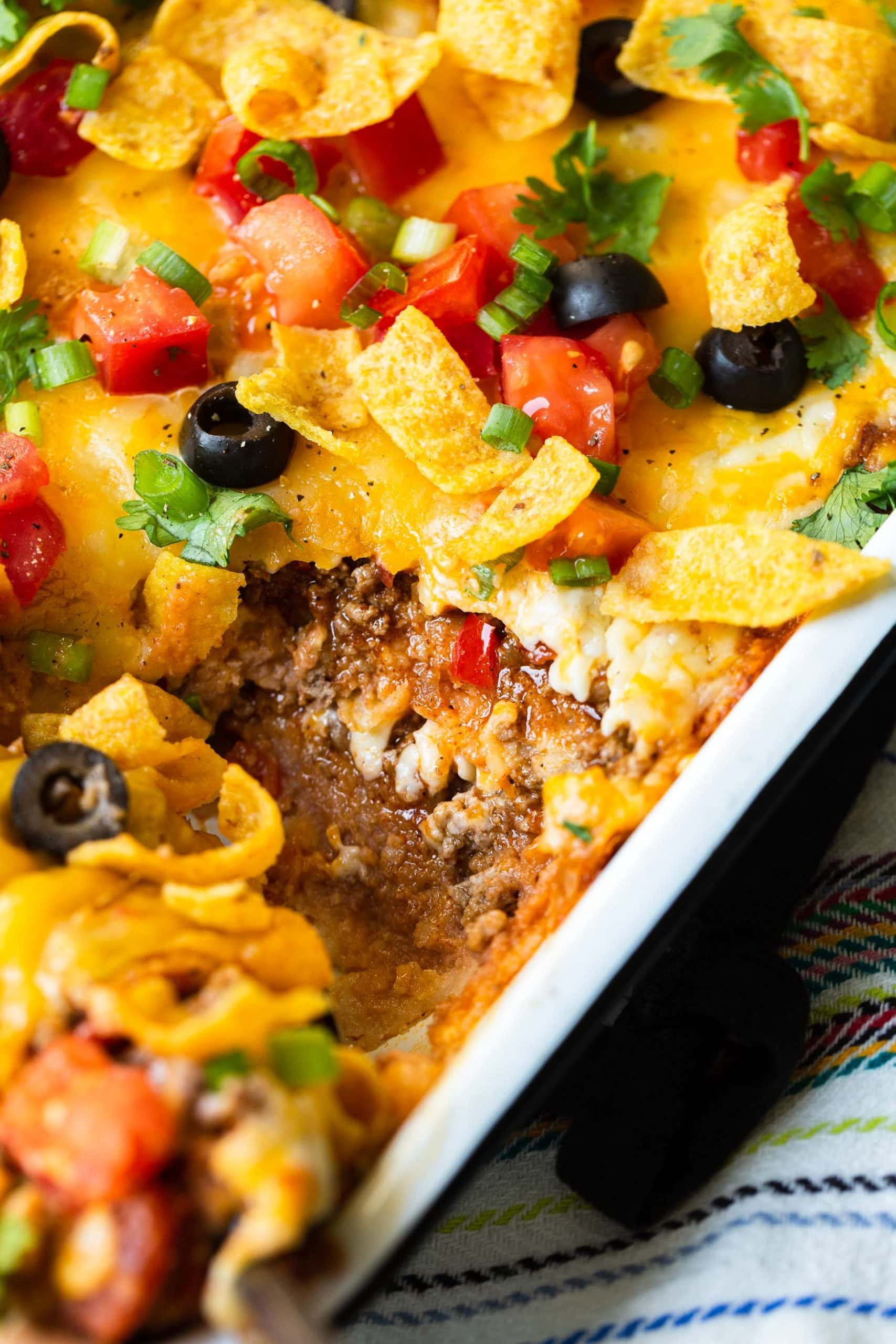 a close up photo of a taco casserole in the dish and one piece is missing so you can see the layer inside.