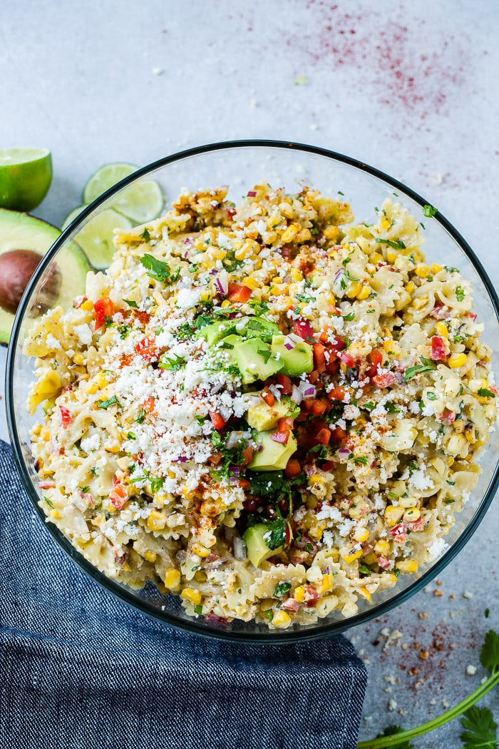 photo of a bow tie pasta salad with avocados, peppers, grilled corn, cilantro, and cotija cheese making up an Elote Mexican Corn Pasta Salad