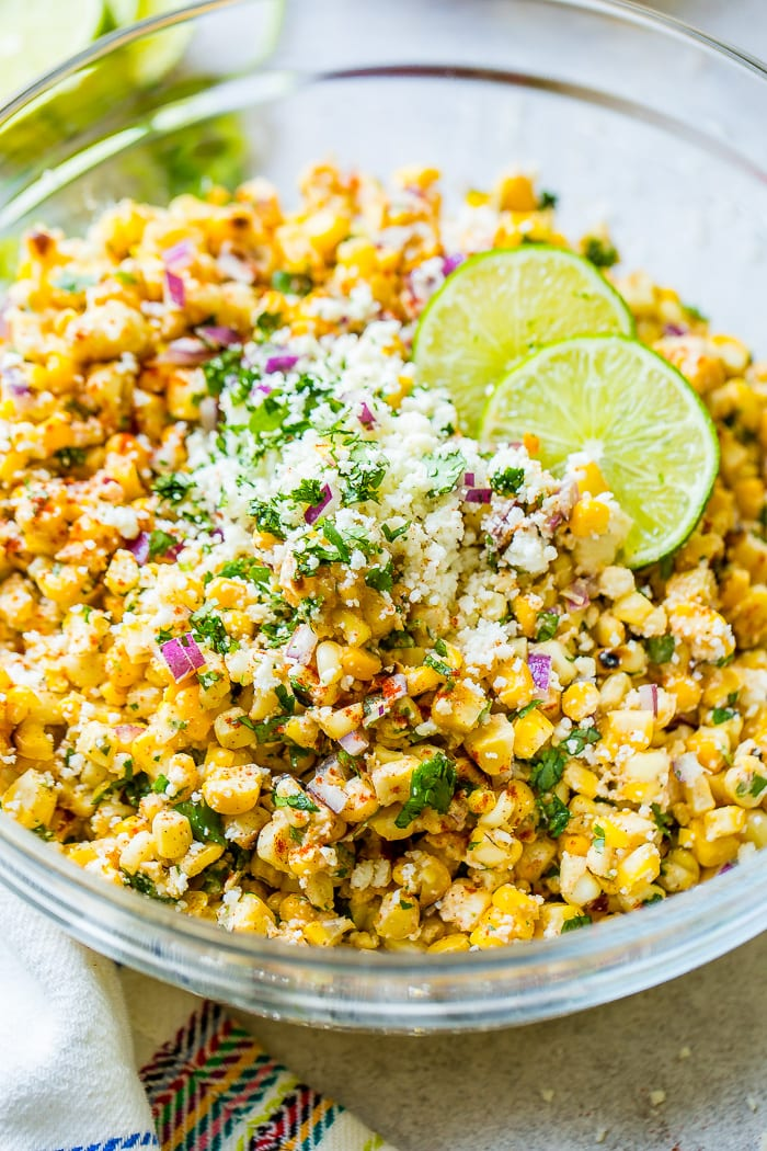 A glass bowl full of grilled corn, red onions, cilantro, crema, cotija cheese and lime juice which makes the best elote mexican grilled corn salad