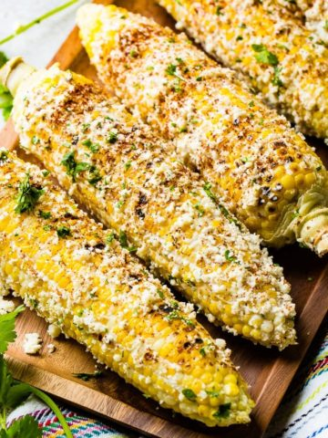 A photo of several cobs of elote mexican street corn lathered in cotija cheese and seasonings.
