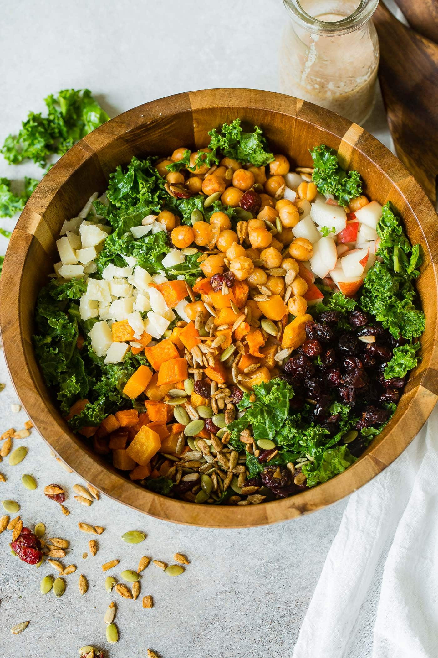 A photo of a large wooden bowl full of kale salad topped with roasted butternut squash, craisins, chickpeas, pepitas, apples and gouda cheese.