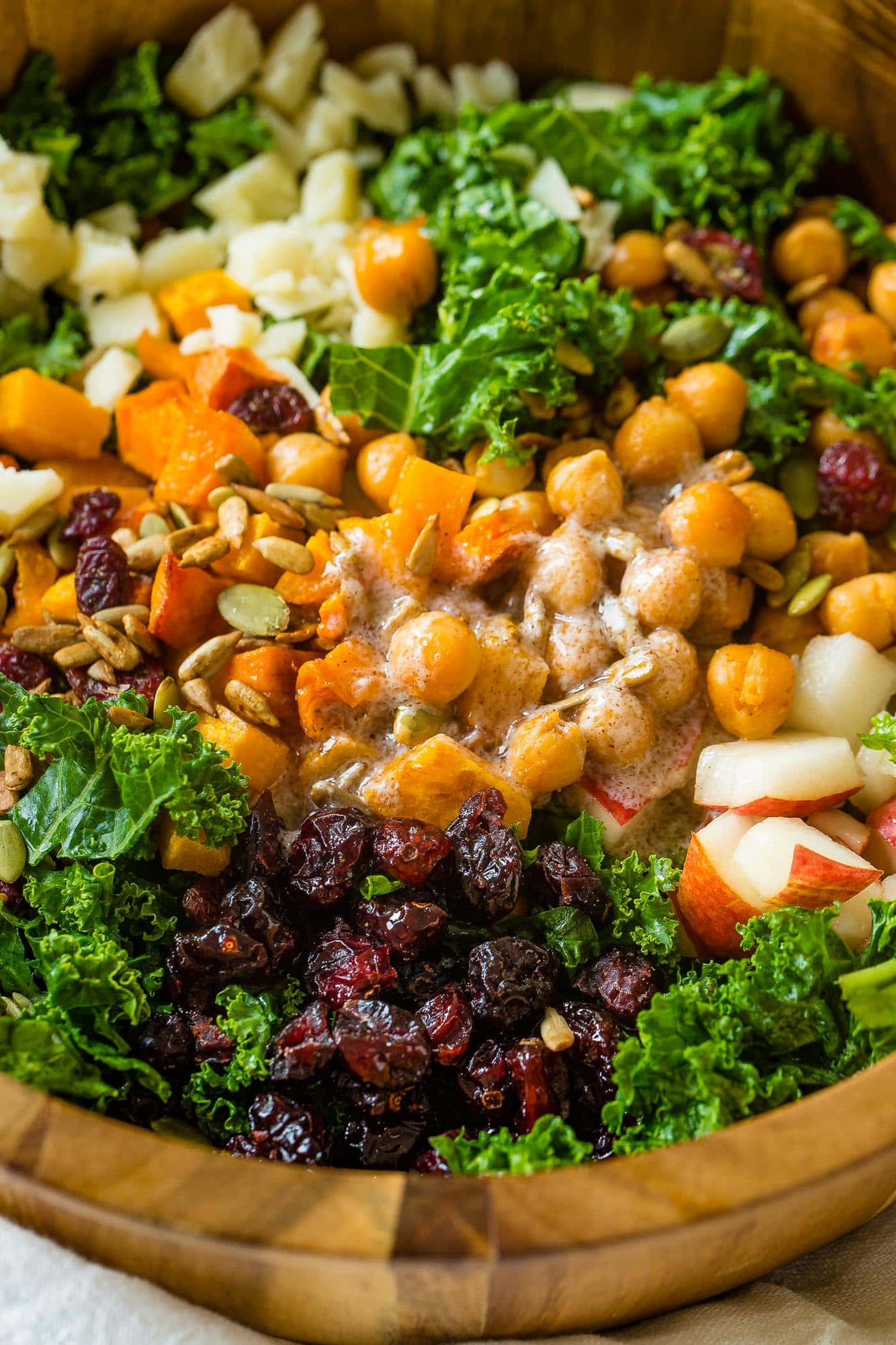 A photo of a large wooden bowl full of kale salad topped with roasted butternut squash, craisins, chickpeas, pepitas, and gouda cheese with dressing that needs to be stirred in.