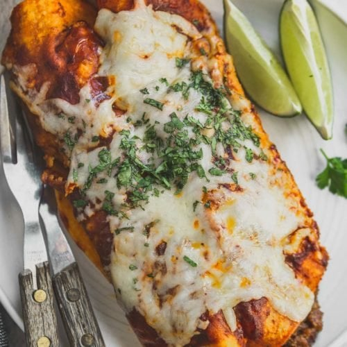 Two enchiladas on a dinner plate with lime wedges and silverware. The enchiladas are covered with melted cheese and chopped cilantro.