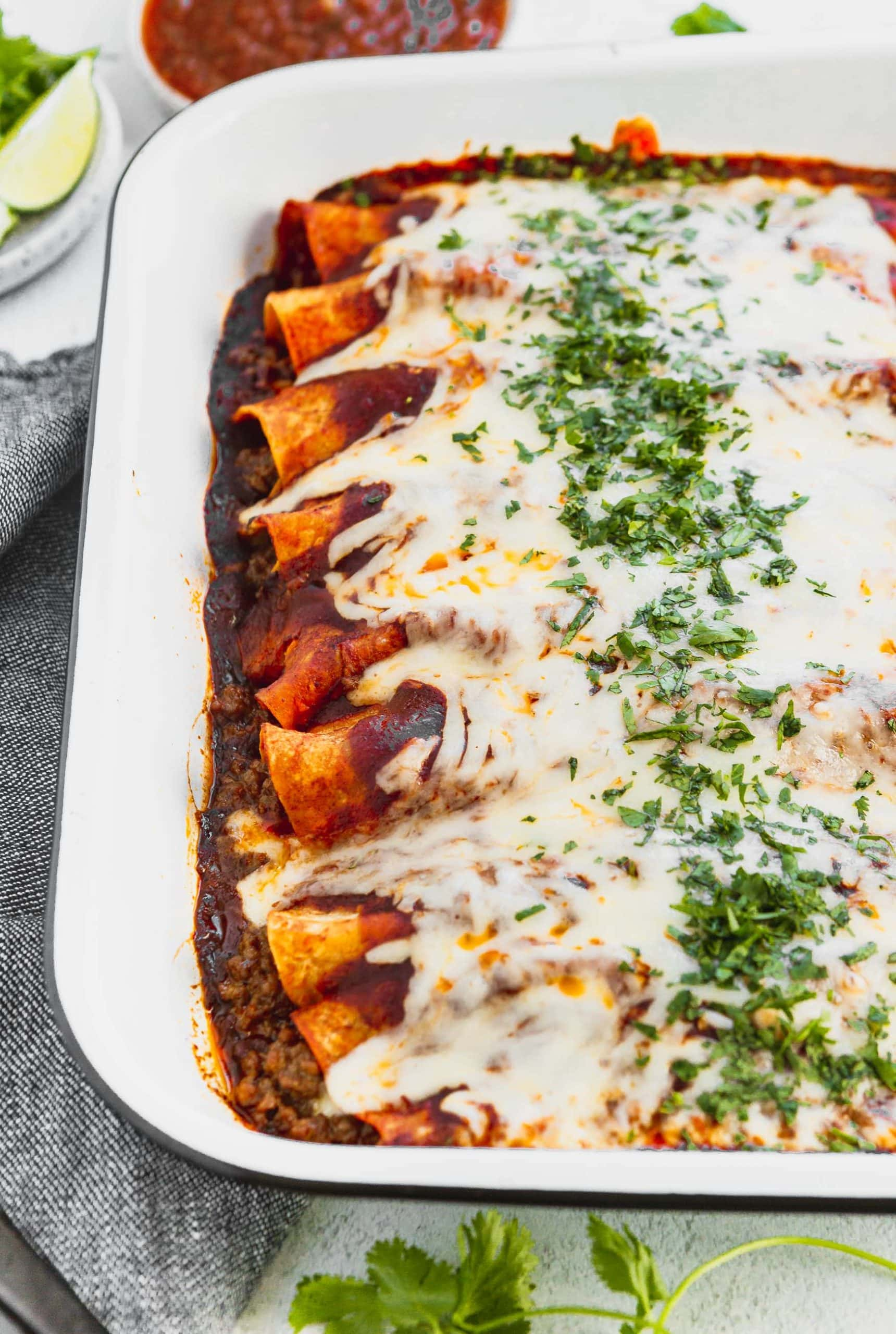 A photo of a pan of beef enchiladas covered in melted cheese and finely chopped cilantro.