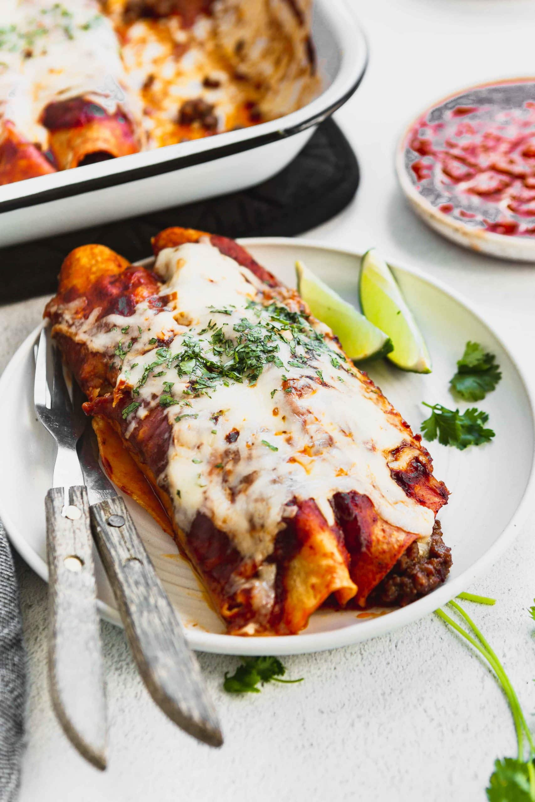 A photo of two ground beef enchiladas on a white plate with two lime wedges on the side.