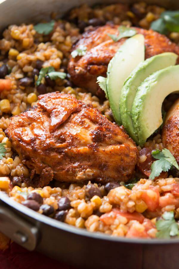 It's a one skillet wonder! Mexican Fiesta Chicken and Rice served with fresh cilantro and a creamy avocado. It's healthier too with brown rice!