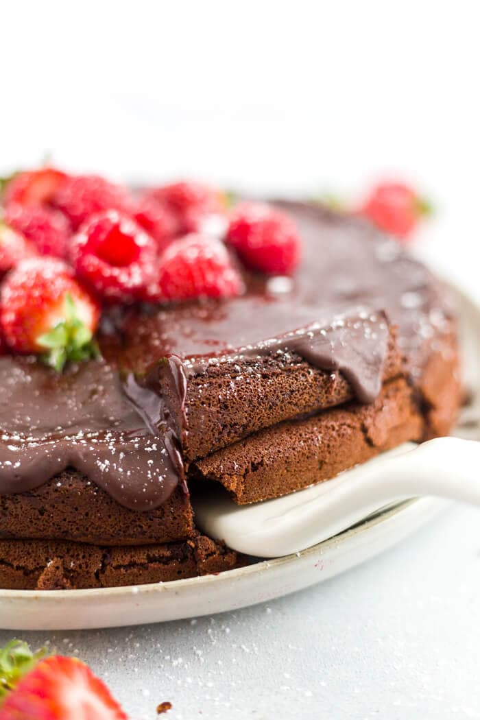 serving a slice of gluten free chocolate cake topped with fresh berries