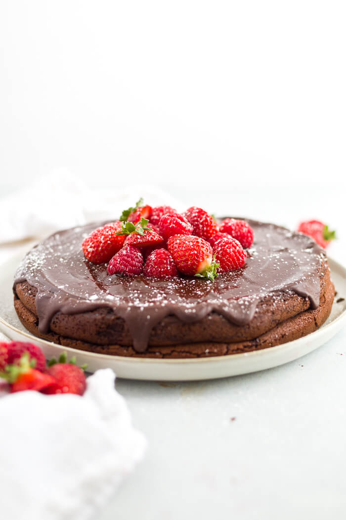 flourless chocolate cake on white platter garnished with strawberries