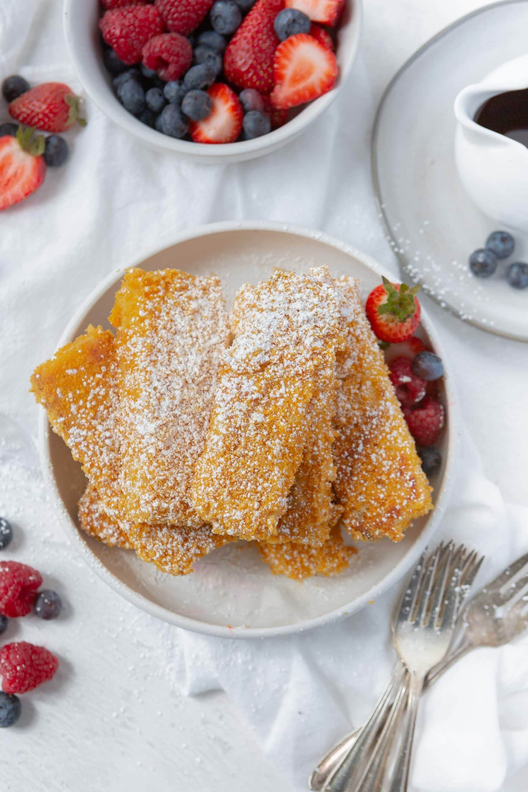 A dish stacked with French Toast sticks. The French toast is golden brown and sprinkled with powdered sugar. There are three forks next to the plate and sliced strawberries are around the French toast.