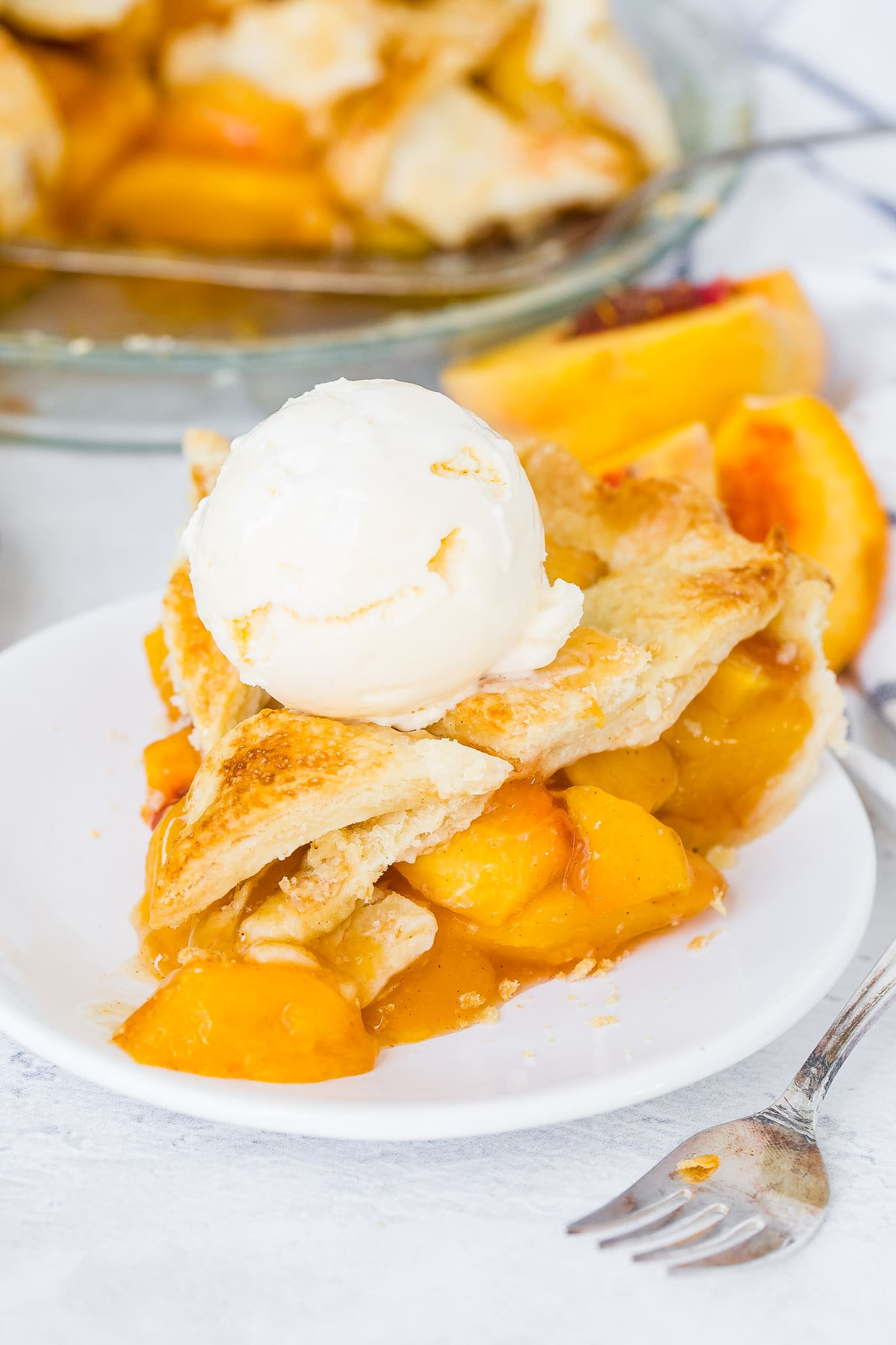 A photo of a slice of fresh peach pie with lattice crust on a white plate with a scoop of vanilla ice cream on top.