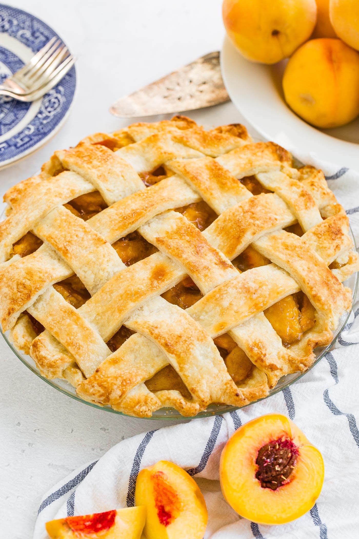 A photo of a fresh peach pie with a beautiful golden lattice crust.