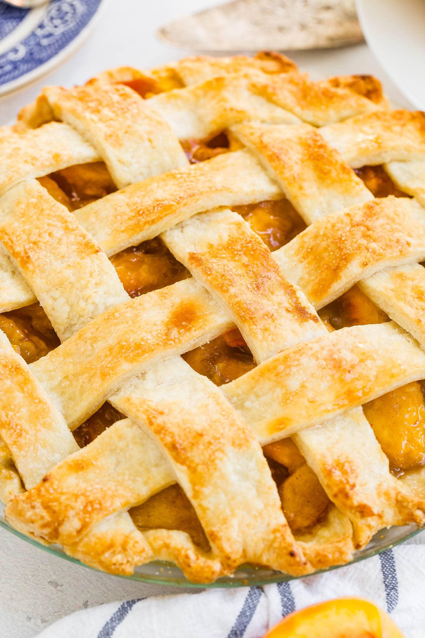 A photo of a fresh peach pie with lattice crust.