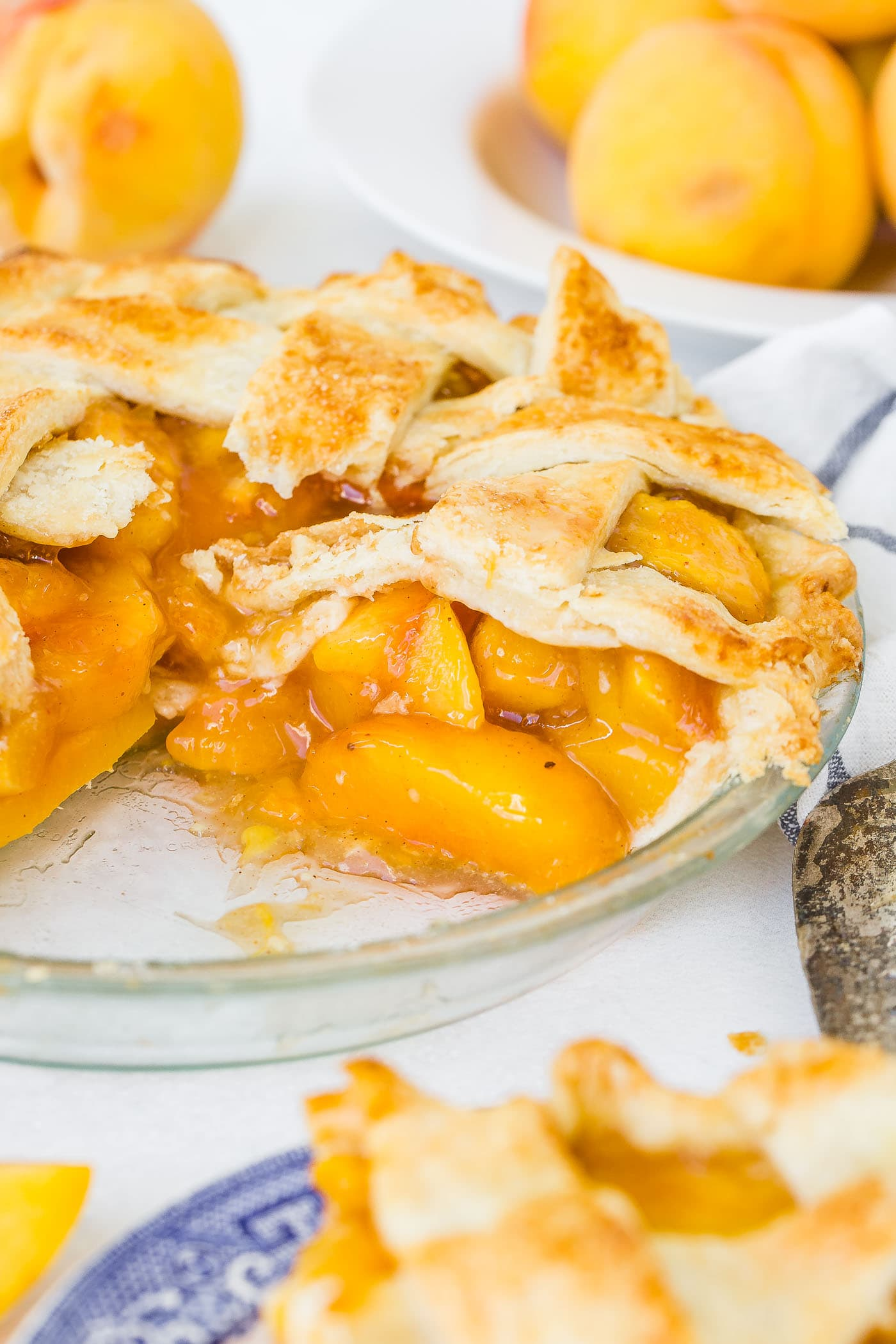A photo of a fresh peach pie with a couple of slices missing and one slice ready to serve.