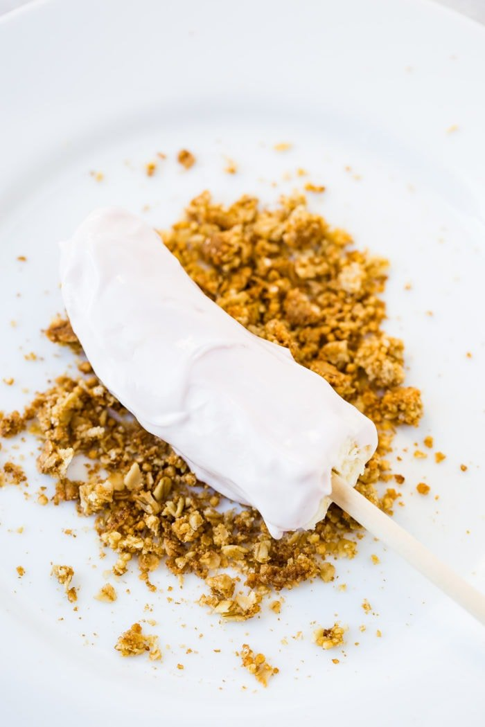 a white plate with a strawberry greek yogurt dipped banana being rolled in granola