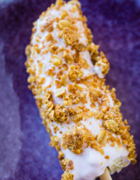 a bright purple plate with a frozen banana dipped in greek yogurt and rolled in granola