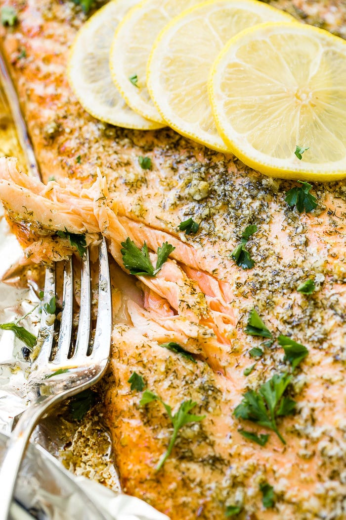 A close up photo of a baked salmon filet flaked with a fork, garnished with dill and fresh parsley, and sitting on aluminum foil