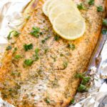 A photo of a baked salmon filet sitting in aluminum foil garnished with fresh parsley and four lemon slices