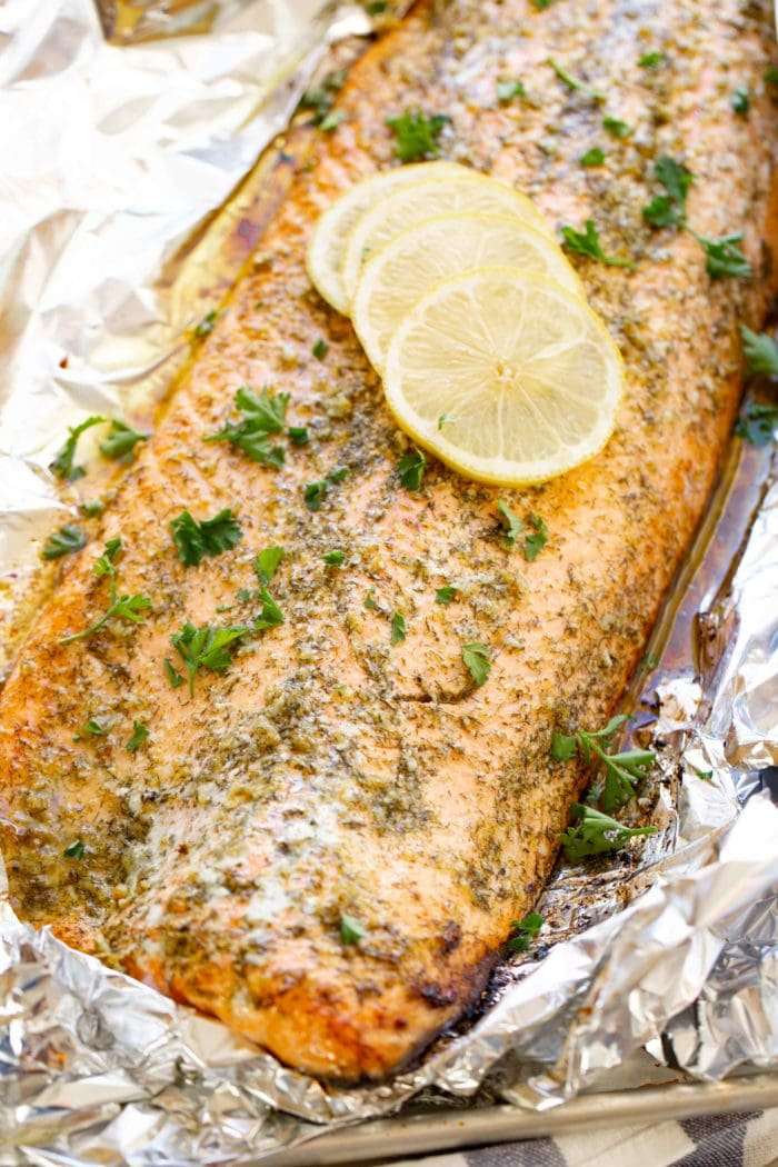 A photo of a baked salmon filet sitting in aluminum foil garnished with fresh parsley and for lemon slices