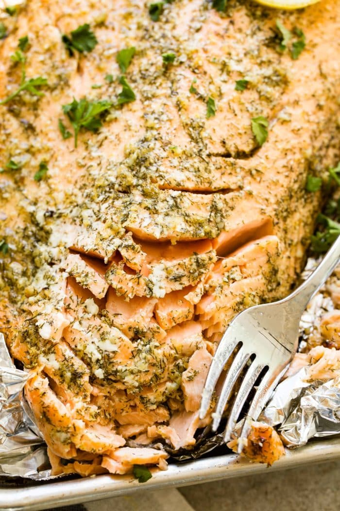 A photo of a baked salmon filet flaked with a fork, garnished with fresh parsley, and sitting on a foil and