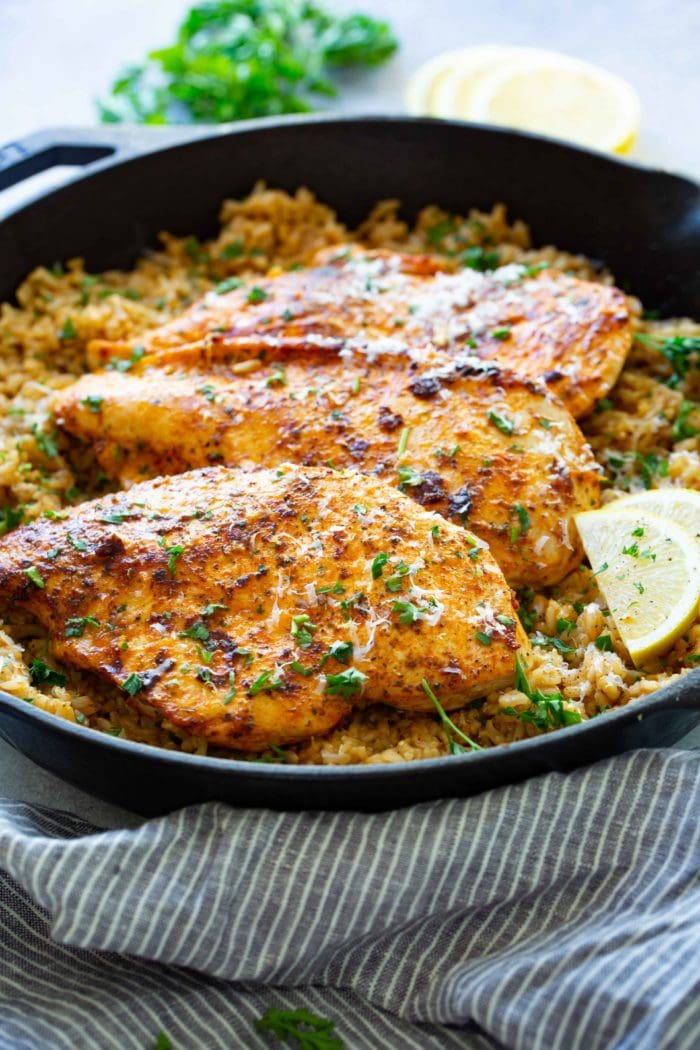a cast iron pan full of simple garlic butter parmesan chicken with lemon rice