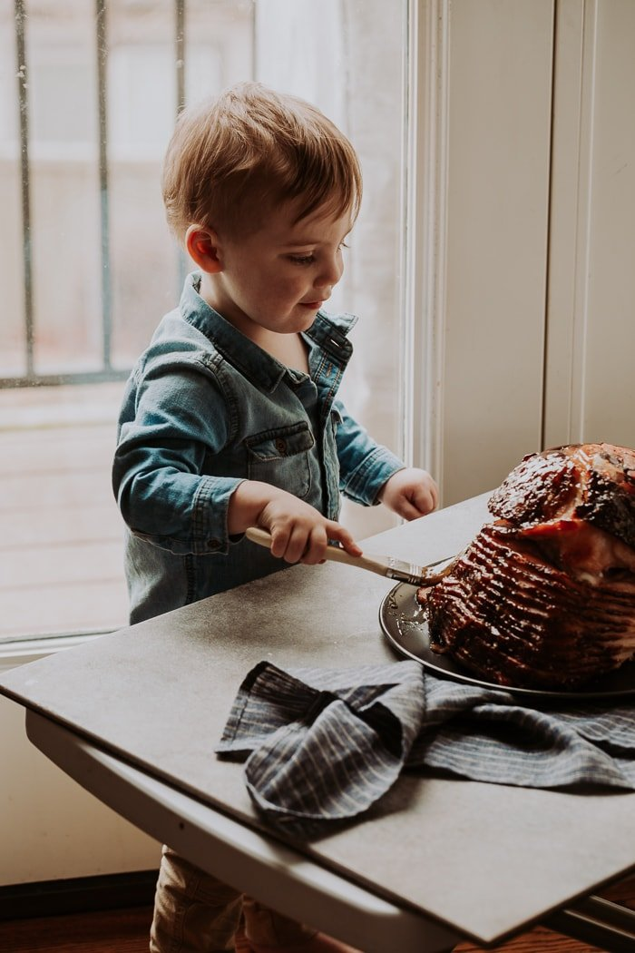A toddler brushing glaze on a spiral ham