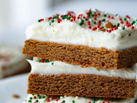 A photo of three gingerbread bars frosted with cream cheese frosting stacked on top of each other.