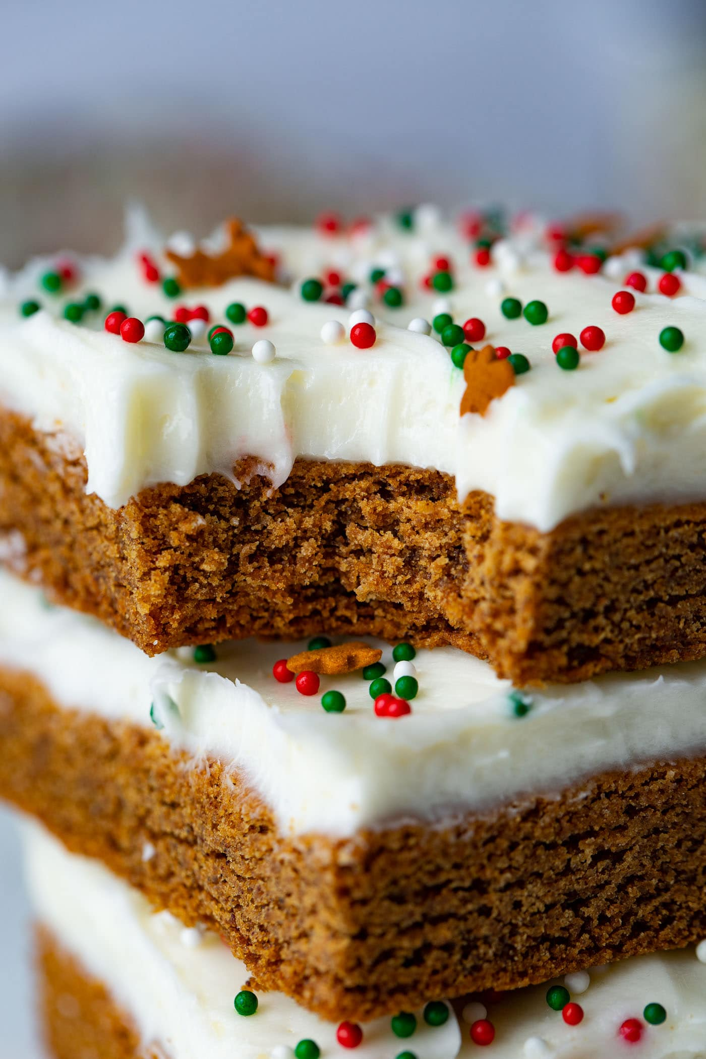 A stack of gingerbread bars frosted with cream cheese frosting and bite taken out of the top bar.