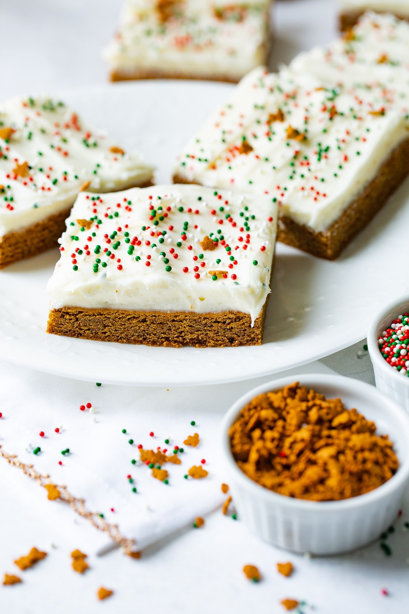 A photo of gingerbread bas sitting on a white plate with cream cheese frosting and holiday sprinkles.