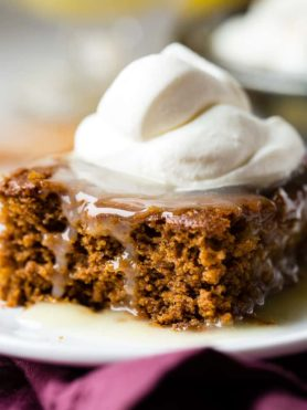 a warm slice of gingerbread cake with lemon sauce and a dollop of whipped cream
