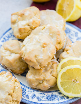 a pile of glazed lemon cookies on a blue floral vintage plate with slices of lemon