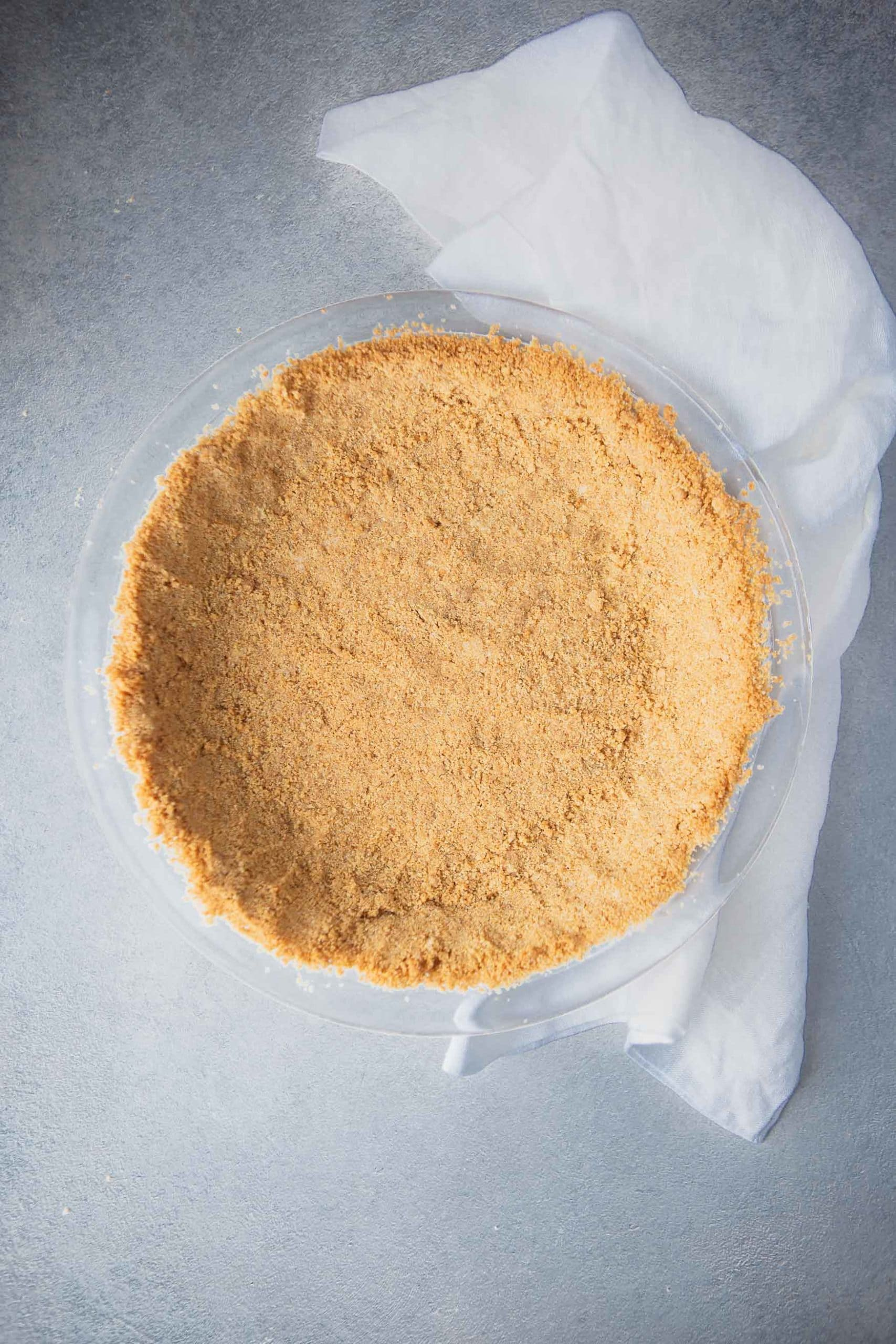 Graham cracker crust that has been pressed into a pie dish and is ready to bake.