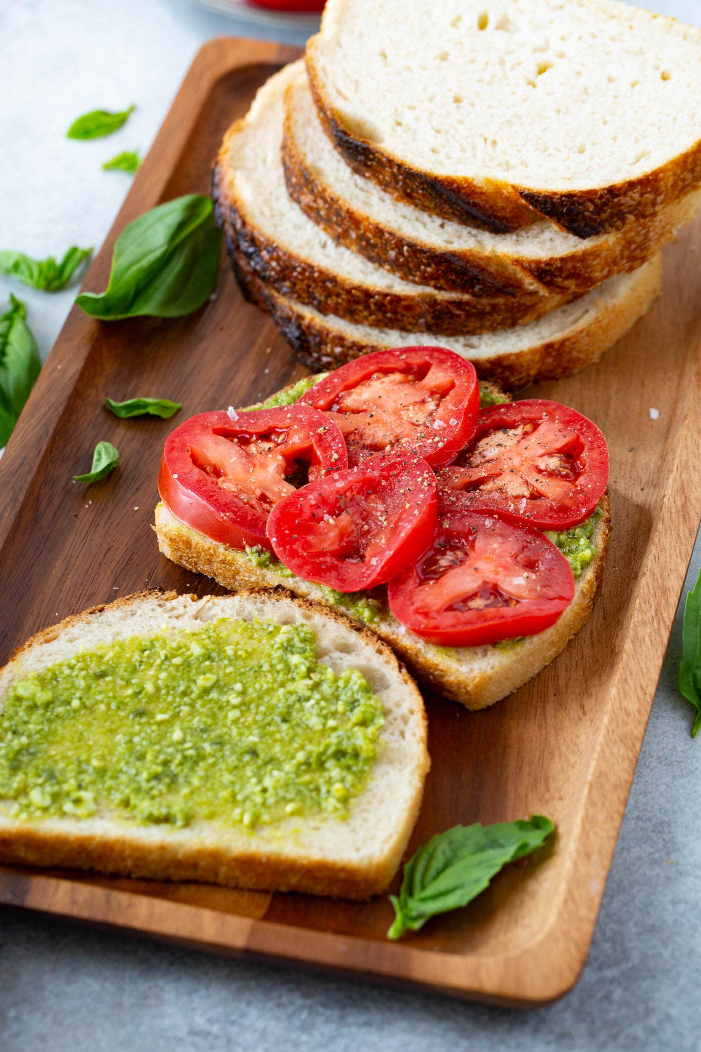 A stack of four slices of bread in the background with a slice of bread that has arugula and five slices of tomatoes on top. Another slice of bread that has been spread with pesto is laying next to it. There are basil leaves scattered on the wooden tray.
