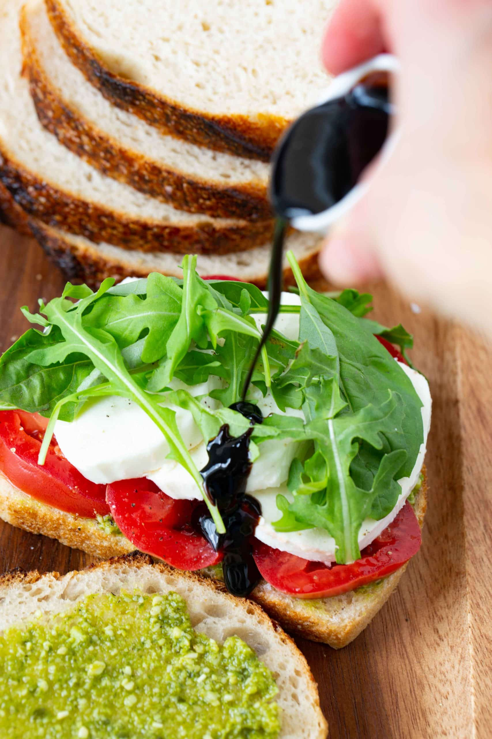 An opened sandwich with sliced tomatoes, sliced fresh mozzarella cheese, and arugula. A balsamic glaze is being drizzled over the top. There is another slice of bread that has been spread with pesto in front of it. there are four slices of bread stacked in the background.