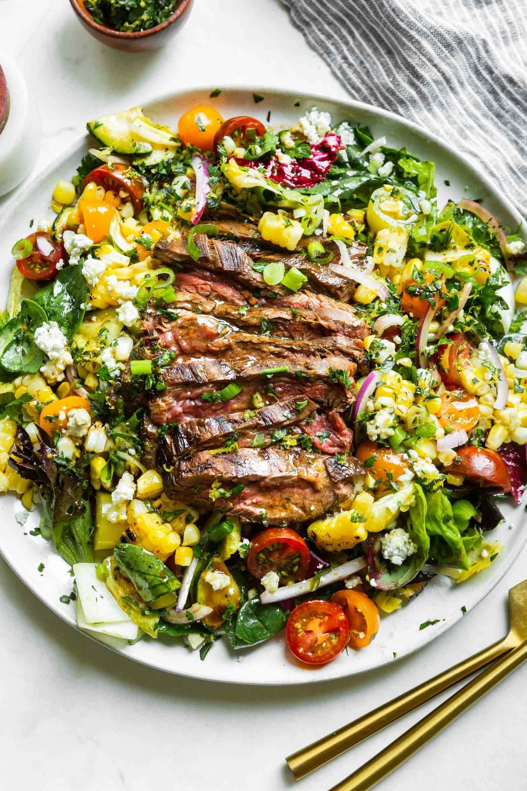 a photo of a large white plate full of a grilled steak and gorgonzola salad topped with grilled corn and gorgonzola cheese.