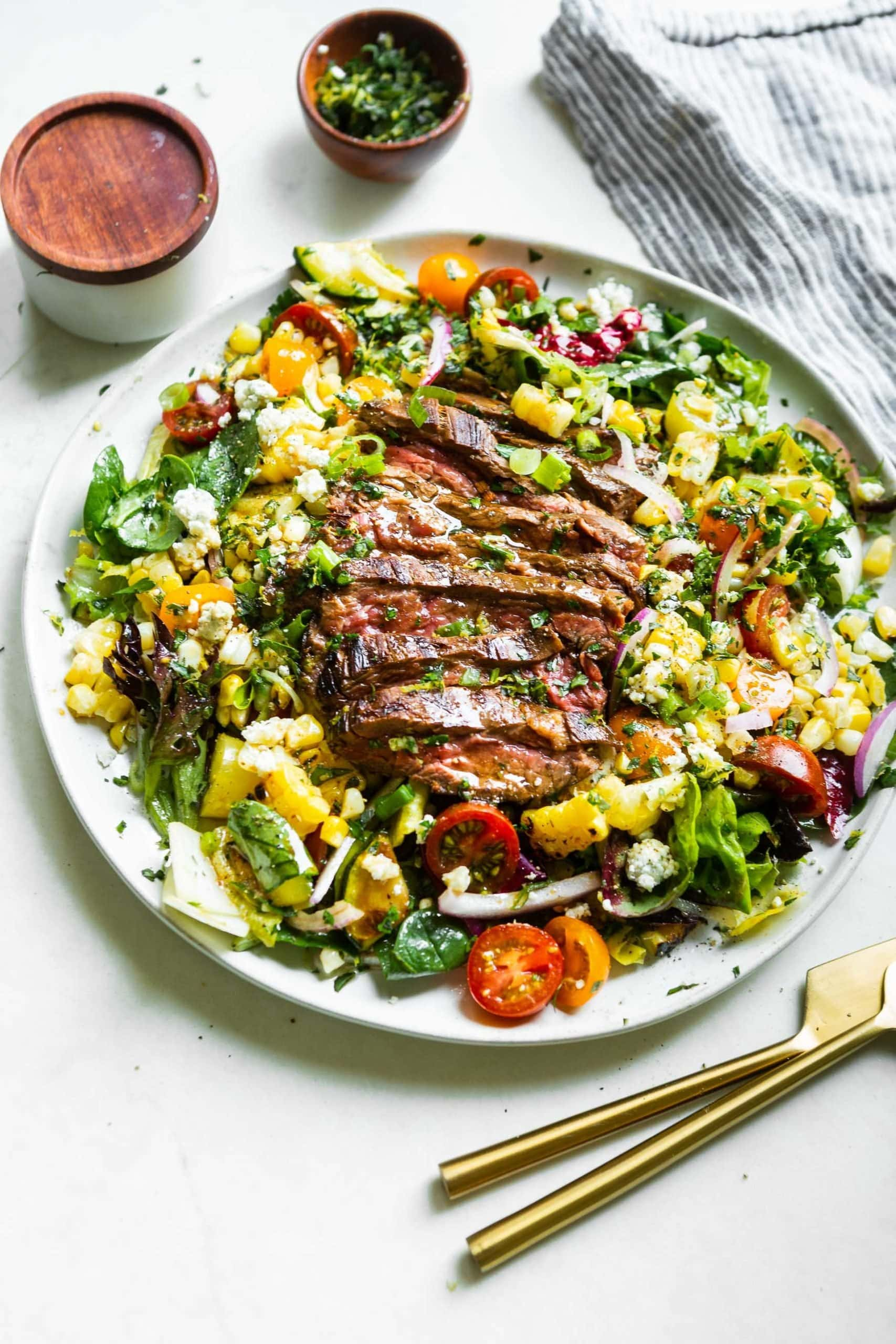 a photo of a plate full of grilled corn and gorgonzola steak salad.