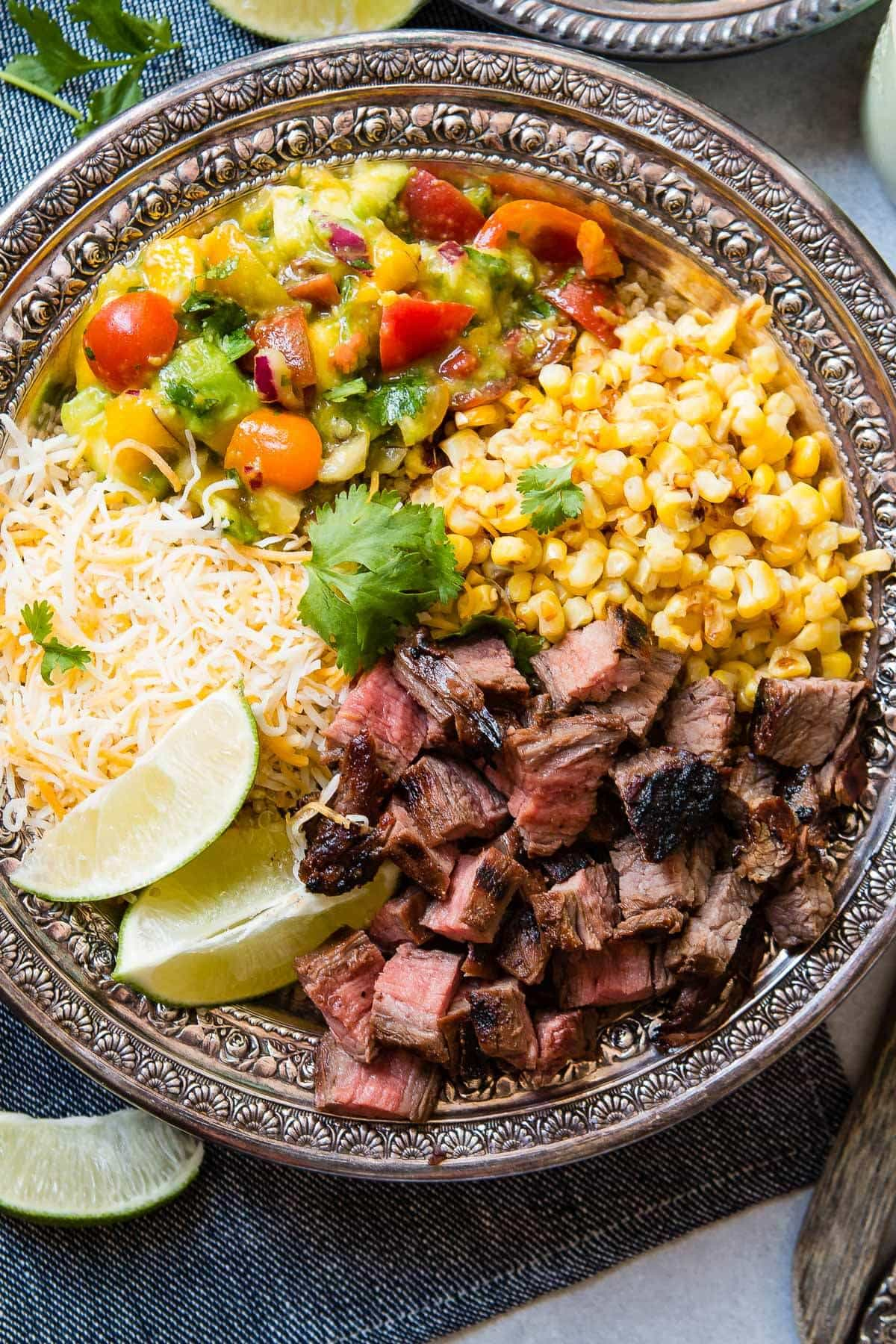 Easy Grilled Steak Burrito Bowls are great for easy meal prep recipes full of corn, quinoa, a killer mango avocado salsa and more!