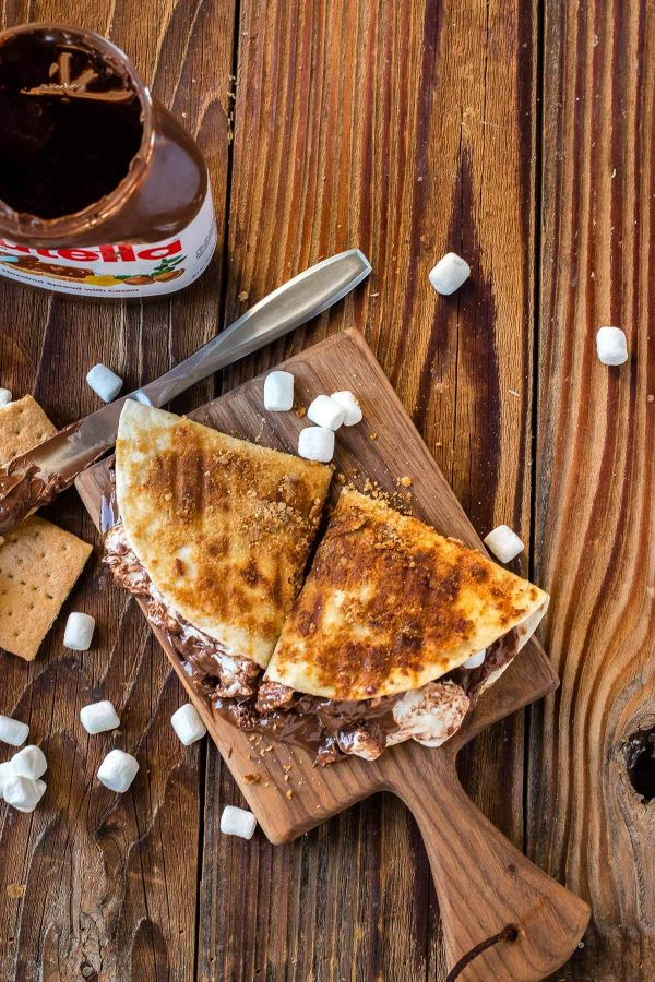Dessert quesadilla with nutella and marshmallows on a cutting board after being grilled on the bbq ohsweetbasil.com