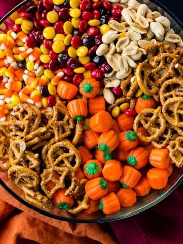 a glass bowl full of candy corn, pretzles, m&ms, peanuts and candy pumpkins