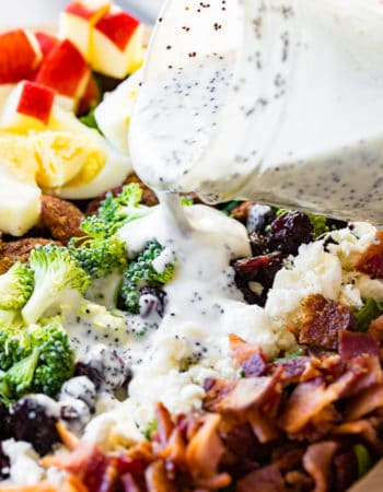 a wooden bowl full of a harvest cobb salad with maple poppy seed dressing. Hardboiled eggs, brown sugar pecans, broccoli, craisins, apples, feta and kale