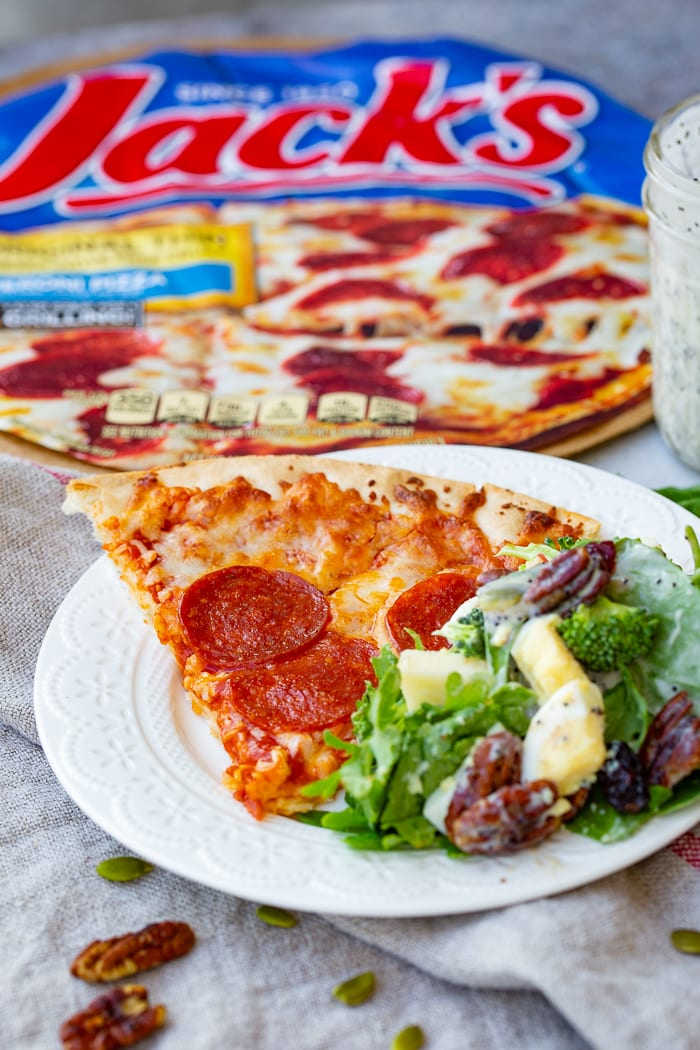 A white plate with a slice of pepperoni pizza and harvest cobb salad with Jack's pizza behind it