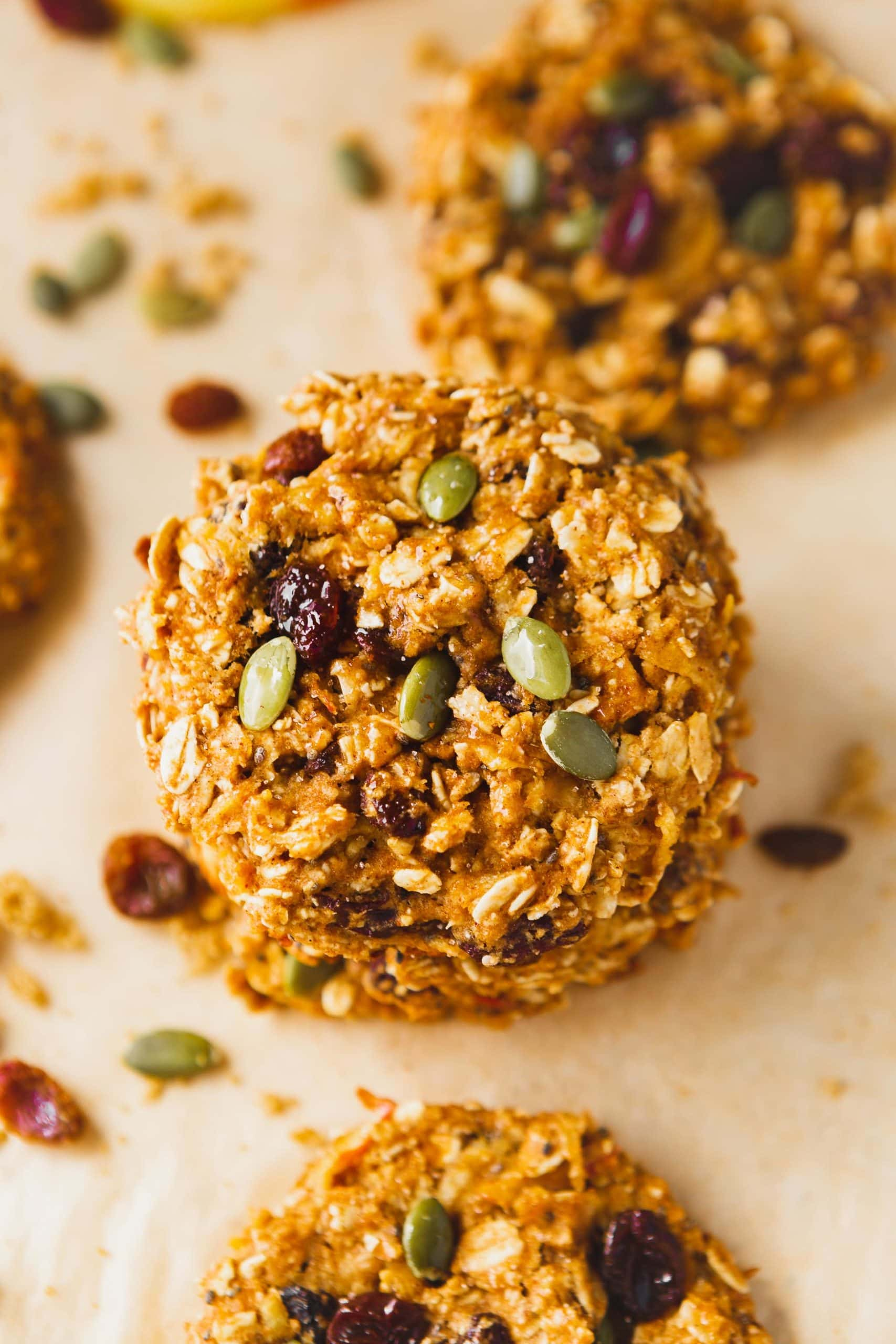 a photo of two healthy breakfast cookies stacked on each other full of raisins and pepitas