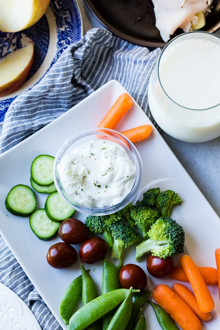 A white dish with broccoli, carrots, cucumbers and tomatoes with a small dish of healthy herb veggie dip with greek yogurt and ranch!