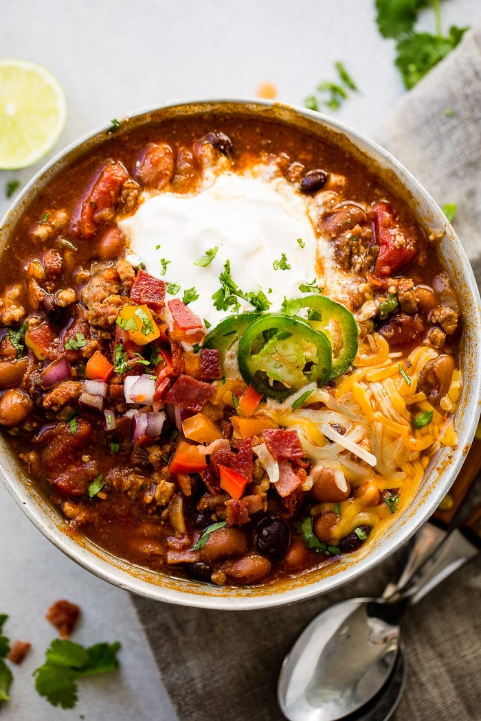 A metal bowl of ground turkey chili full of beans, red onions that have been chopped, chopped peppers , jalapeno slices on melted cheese next to a dollop of sour cream with a dash of cilantro