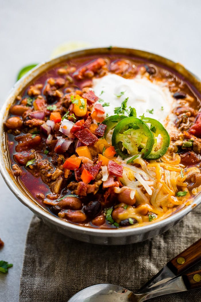 A metal bowl of ground turkey chili full of beans, red onions that have been chopped, chopped peppers , jalapeno slices on melted cheese next to a dollop of sour cream with a dash of cilantro and a grey napkin underneath with two wooden handled spoons to the side.