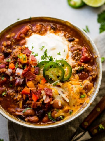 Award winning healthy turkey instant pot chili A metal bowl of ground turkey chili full of beans, red onions that have been chopped, chopped peppers , jalapeno slices on melted cheese next to a dollop of sour cream with a dash of cilantro and a grey napkin underneath
