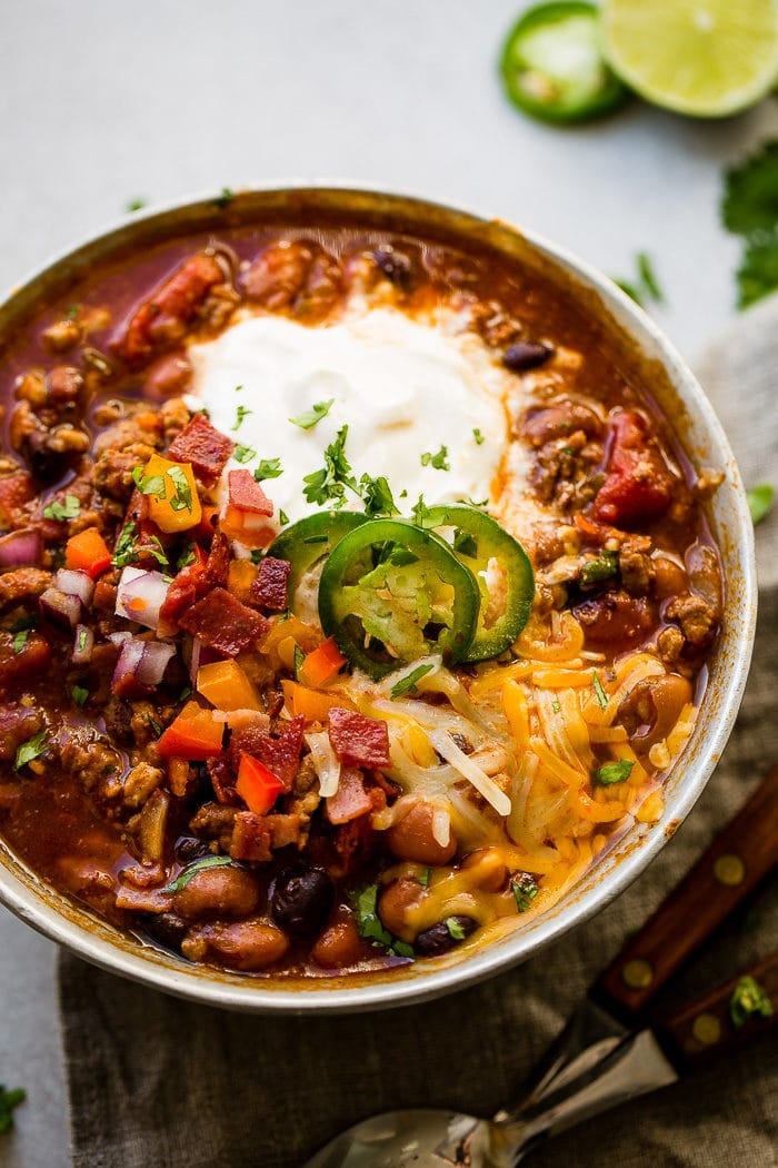 A metal bowl of ground turkey chili full of beans, red onions that have been chopped, chopped peppers , jalapeno slices on melted cheese next to a dollop of sour cream with a dash of cilantro and a grey napkin underneath