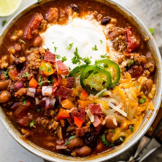 A metal bowl of ground turkey chili full of beans, red onions that have been chopped, chopped peppers , jalapeno slices on melted cheese next to a dollop of sour cream with a dash of cilantro and a grey napkin underneath with two wooden handled spoons to the side. Award winning healthy turkey instant pot chili