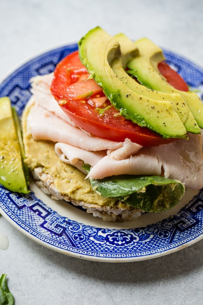 a blue plate with a rice cake loaded with hummus, lettuce, turkey, tomato and avocado!