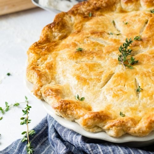 A chicken pot pie, baked to a perfect golden brown with a sprig of fresh thyme on top. The pie dish is sitting on a blue and white striped kitchen towel.